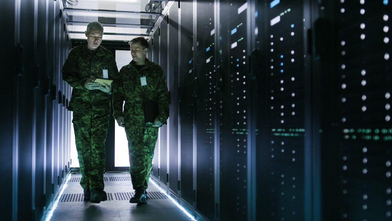 Two men in military uniform walking in data server room under OpSec